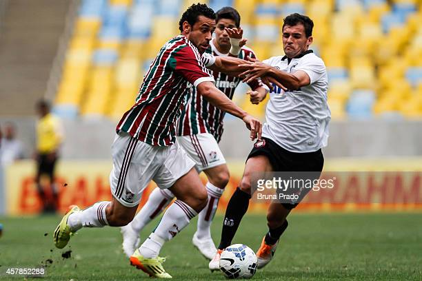 Fred of Fluminense struggles for the ball with Paulinho Dias of Atletico PR during a match between Fluminense and Atletico PR at Maracana Stadium on...