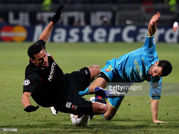 Fred of Lyon is tripped by Gianluca Zambrotta of Barcelona during the UEFA Champions League Group E match between Lyon and Barcelona at the Stade...