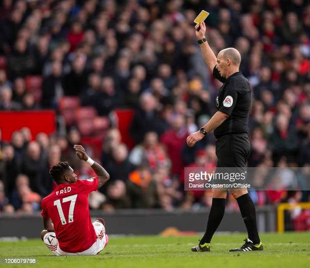Fred of Manchester United is shown a yellow card and is booked by referee Mike Dean during the Premier League match between Manchester United and...