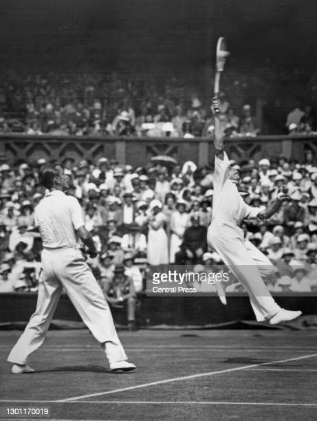 Fred Perry of Great Britain jumping to make an overhead smash return against Christian Boussus and Antoine Gentien of France as playing partner Pat...