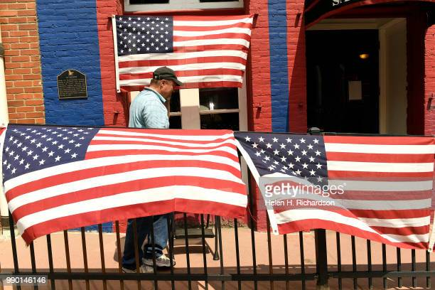Fred Poston puts up a flag display along Gregory street as he helps prepare the downtown streets for the Fourth of July holiday on July 2 2018 in...