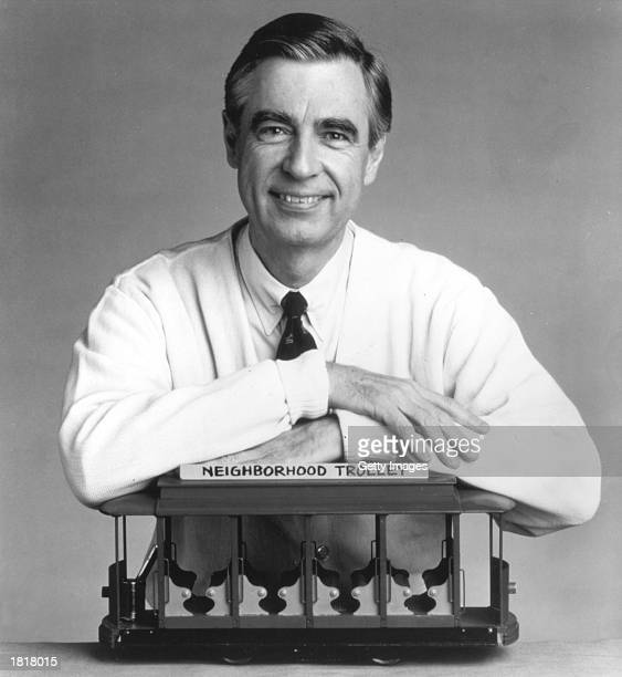 Fred Rogers the host of the children's television series Mr Rogers' Neighborhood rests his arms on a small trolley in this promotional portrait from...