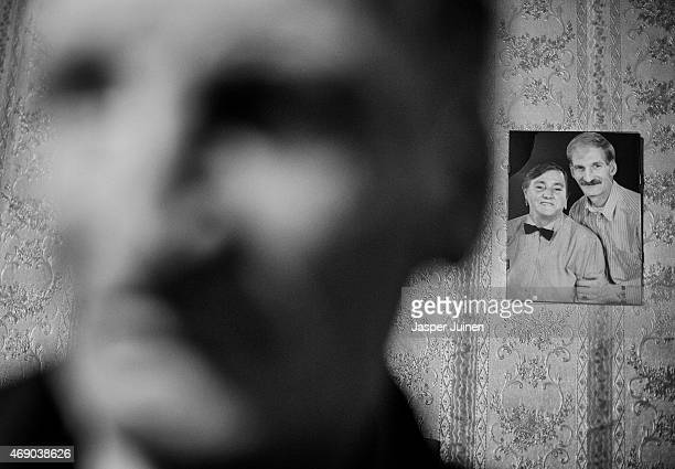 Fred Schiphorst stands in his living room besides his wedding picture dating back to October 10 hanging from a wall of him and his second wife...