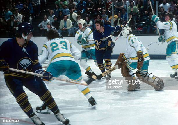 Fred Stanfield of the Buffalo Sabres skates on the ice as goalie Gilles Meloche of the California Golden Seals defends the net circa 1976 at the...