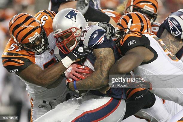 Fred Taylor of the New England Patriots is stopped as he runs the ball by Dhani Jones and Keith Rivers of the Cincinnati Bengals during their...