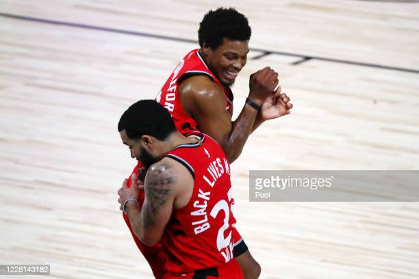 Fred VanVleet of the Toronto Raptors celebrates with Kyle Lowry of the Toronto Raptors after making a half court shot against the Brooklyn Nets to...