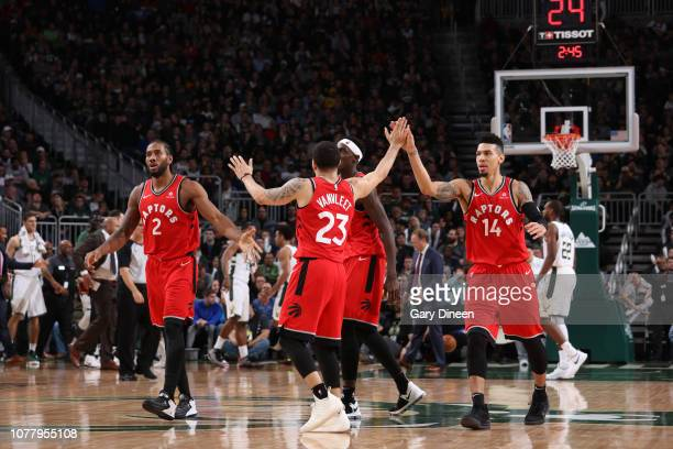 Fred VanVleet of the Toronto Raptors hi fives teammates during the game against the Milwaukee Bucks on January 5 2019 at the Fiserv Forum Center in...