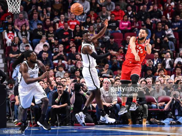 Fred VanVleet of the Toronto Raptors plays the ball past Caris LeVert and Kenneth Faried of the Brooklyn Nets during the preseason NBA game at the...