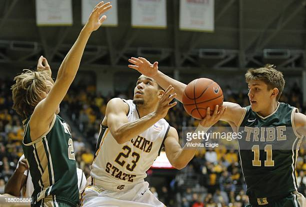 Fred VanVleet of Wichita State drives to the basket against Tim Rusthoven left and Michael Schlotman of William and Mary during the first half on...