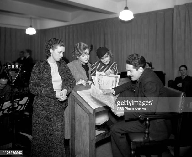Fred Waring conductor and band leader gets ready for a CBS Radio broadcast From left are Rosemary Lane Priscilla Lane Babs Ryan and Fred Waring...