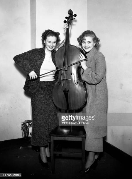 Fred Waring conductor and band leader gets ready for a CBS Radio broadcast Left to right Rosemary and Priscilla Lane December 1 1933