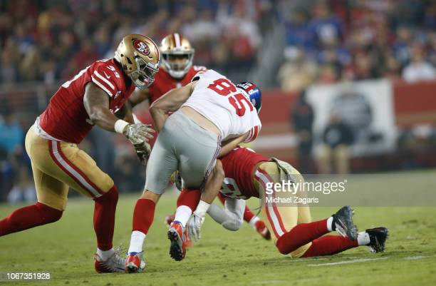 Fred Warner and DeForest Buckner of the San Francisco 49ers tackle Rhett Ellison of the New York Giants during the game at Levi's Stadium on November...