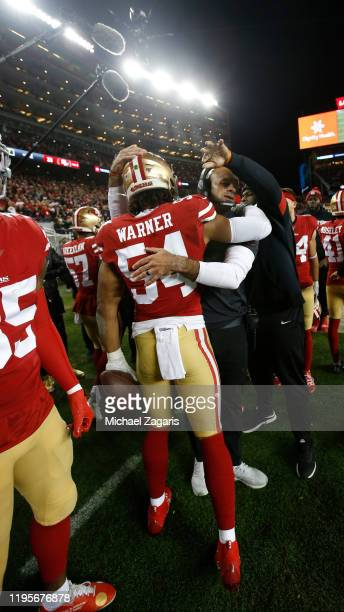 Fred Warner of the San Francisco 49ers is congratulated by Defensive Coordinator Robert Saleh on the sideline after returning an interception for a...