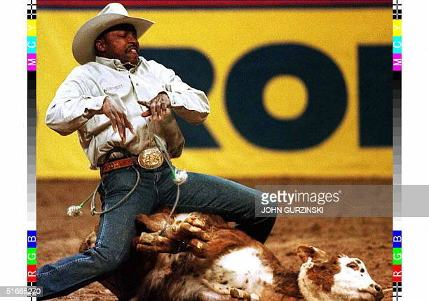 Fred Whitfield releases the ties and throws his arms into the air to signal that the calf is roped during the Calf Roping event at the National...