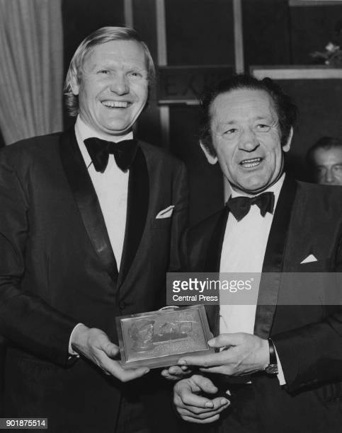 Fred Winter presents English National Hunt racing jockey Terry Biddlecombe with a plaque from the Ladbroke Club upon his retirement 26th March 1974