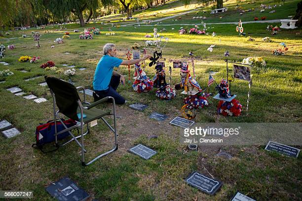 Fred Wodnicki from North Hollywood tends to decorations he maintains where his four pets are buried at the Los Angeles Pet Memorial Park and...