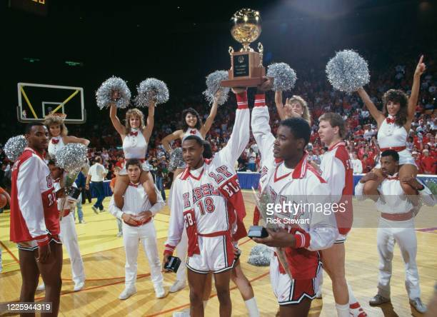 Freddie Banks and Gary Graham, Guards for the University of Las Vegas Nevada Rebels hold the trophy aloft and celebrate with their team after winning...
