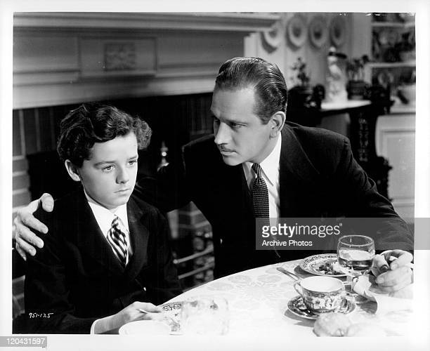 Freddie Bartholomew being embraced by Melvyn Douglas at the table in a scene from the film 'Captains Courageous' 1937