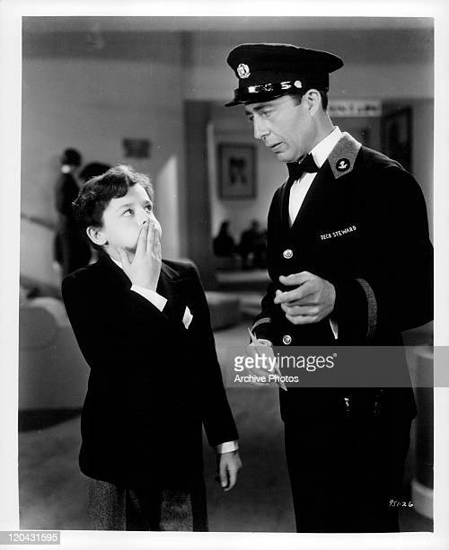 Freddie Bartholomew holding mouth in front of deck steward in a scene from the film 'Captains Courageous' 1937
