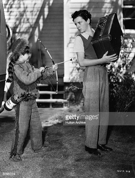 Freddie Bartholomew is not amused at being the target of bow and arrowwielding Scotty Beckett in the musical comedy 'Listen Darling' directed by...