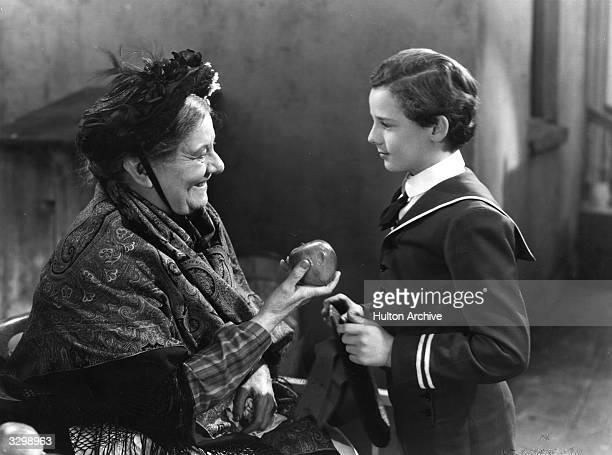 Freddie Bartholomew receives an apple from Jessie Ralph in a scene from 'Little Lord Fauntleroy' adapted from the novel by Frances Hodgson Burnett...