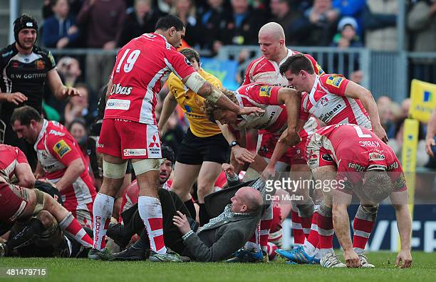 Freddie Burns of Gloucester tackles a pitch invader after Exeter Chiefs go over for a try during the Aviva Premiership match between Exeter Chiefs...