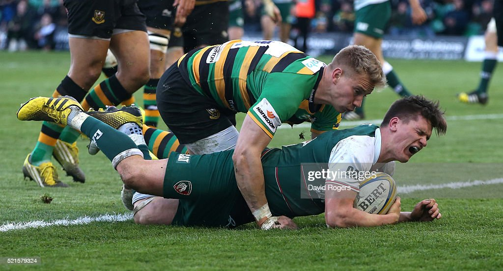 Freddie Burns of Leicester grimaces as Harry Mallinder falls on him as he scores a try during the Aviva Premiership match between Northampton Saints and Leicester Tigers at Franklin's Gardens on April 16, 2016 in Northampton, England.