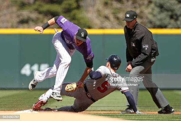 Freddie Freeman of the Atlanta Braves beats the tag of second baseman DJ LeMahieu of the Colorado Rockies for a double in the second inning at Coors...