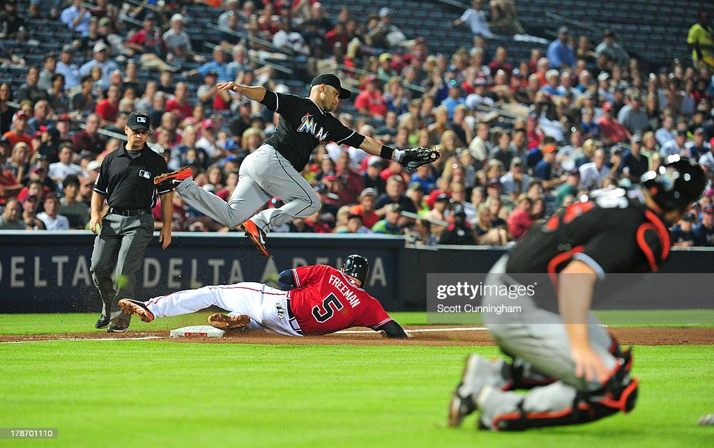 Freddie Freeman #5 of the Atlanta Braves beats the throw to third base by Jeff Mathis #6 to Placido Polanco #30 of the Miami Marlins at Turner Field on August 30, 2013 in Atlanta, Georgia.