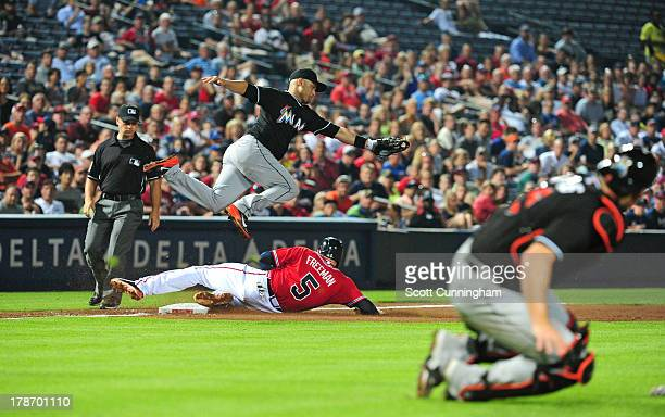 Freddie Freeman of the Atlanta Braves beats the throw to third base by Jeff Mathis to Placido Polanco of the Miami Marlins at Turner Field on August...