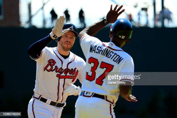 Freddie Freeman of the Atlanta Braves celebrates a tworun home run with third base coach Ron Washington during the fourth inning against the St Louis...