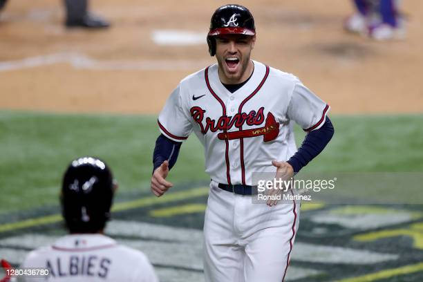 Freddie Freeman of the Atlanta Braves celebrates after scoring a run against the Los Angeles Dodgers during the sixth inning in Game Four of the...