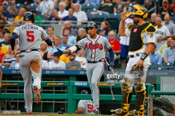 Freddie Freeman of the Atlanta Braves celebrates with Johan Camargo after scoring on a RBI single in the first inning against the Pittsburgh Pirates...