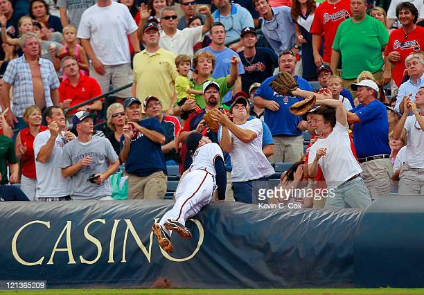 Freddie Freeman of the Atlanta Braves dives into the first row to catch a pop fly foul ball by Pablo Sandoval of the San Francisco Giants at Turner...