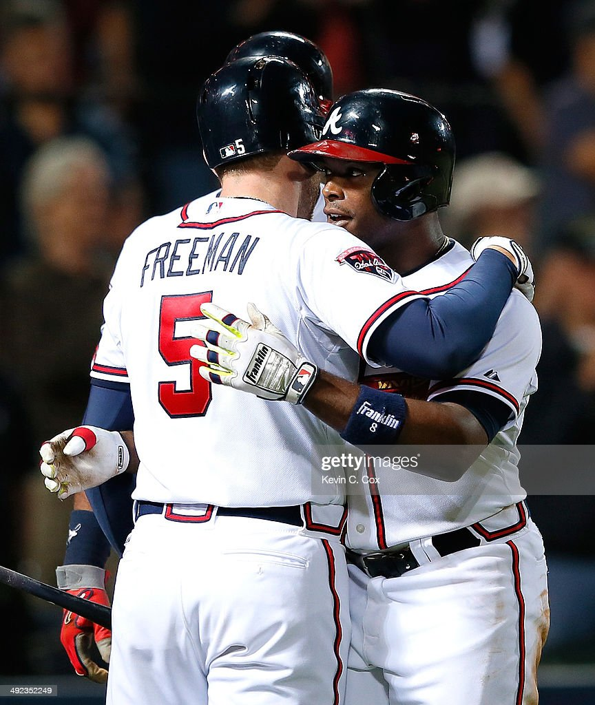 Freddie Freeman #5 of the Atlanta Braves hugs Justin Upton #8 after Upton's two-run homer in the eighth inning against the Milwaukee Brewers that also scored Jason Heyward #22 at Turner Field on May 19, 2014 in Atlanta, Georgia.