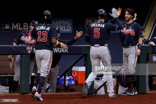 Freddie Freeman of the Atlanta Braves is congratulated by Dansby Swanson after hitting a two run home run against the Los Angeles Dodgers during the...
