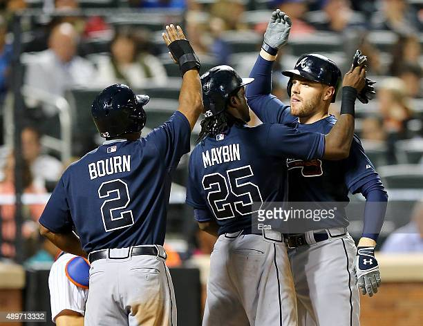 Freddie Freeman of the Atlanta Braves is congratulated by teammaes Michael Bourn and Cameron Maybin after Freeman hit a three run home run in the...