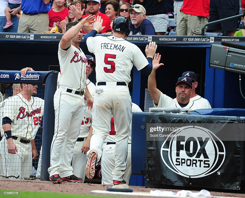 Freddie Freeman #5 of the Atlanta Braves is congratulated by teammates after scoring an eighth inning run against the St. Louis Cardinals at Turner Field on July 27, 2013 in Atlanta, Georgia.