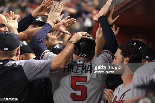 Freddie Freeman of the Atlanta Braves is congratulated in the dugout after scoring in the tenth inning of the MLB game against the Arizona...