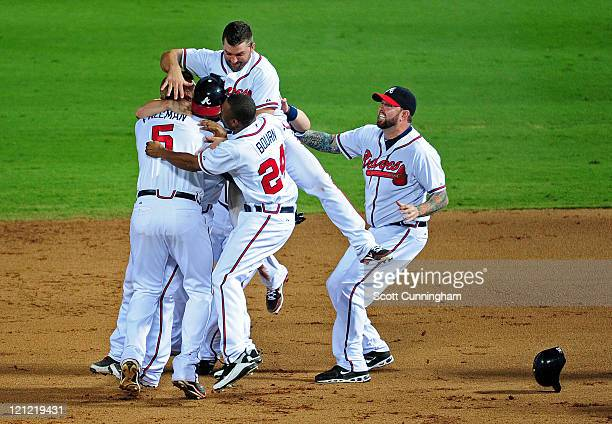 Freddie Freeman of the Atlanta Braves is mobbed by teammates after knocking in the gamewinning run against the San Francisco Giants at Turner Field...