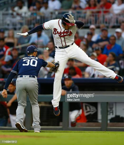 Freddie Freeman of the Atlanta Braves jumps to unsuccessfully avoid a tag by first baseman Eric Hosmer of the San Diego Padres on a ground out in the...
