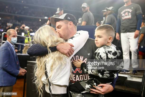 Freddie Freeman of the Atlanta Braves kisses his wife Chelsea while holding his son Charlie following Game Six of the National League Championship...