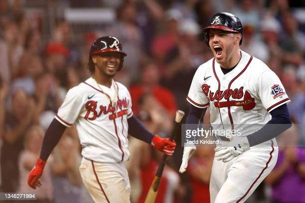 Freddie Freeman of the Atlanta Braves reacts after hitting a home run during the eighth inning against the Milwaukee Brewers in game four of the...