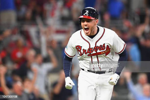 Freddie Freeman of the Atlanta Braves reacts after hitting a solo home run in the sixth inning against the Los Angeles Dodgers during Game Three of...