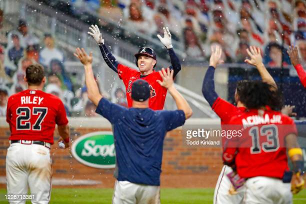 Freddie Freeman of the Atlanta Braves reacts after hitting a two-run home run to win in the eleventh inning of an MLB game against the Boston Red Sox...