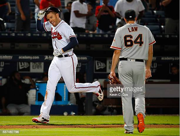 Freddie Freeman of the Atlanta Braves rounds third base after hitting a walk-off homer in their 5-4 win against Derek Law of the San Francisco Giants...