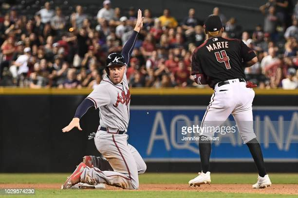Freddie Freeman of the Atlanta Braves safely steals second base in front of Ketel Marte of the Arizona Diamondbacks in the tenth inning of the MLB...