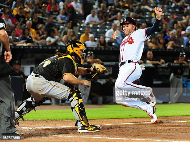 Freddie Freeman of the Atlanta Braves scores a fifth inning run against Eric Fryer of the Pittsburgh Pirates at Turner Field on August 3, 2016 in...