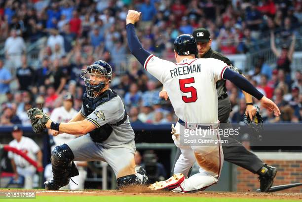 Freddie Freeman of the Atlanta Braves scores a fourth inning run against Erik Kratz of the Milwaukee Brewers at SunTrust Park on August 11 2018 in...