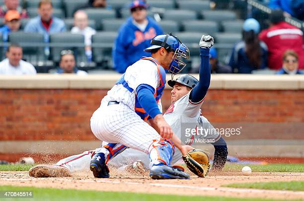 Freddie Freeman of the Atlanta Braves scores a run in the fourth inning ahead of the throw to Anthony Recker of the New York Mets after a sacrifice...